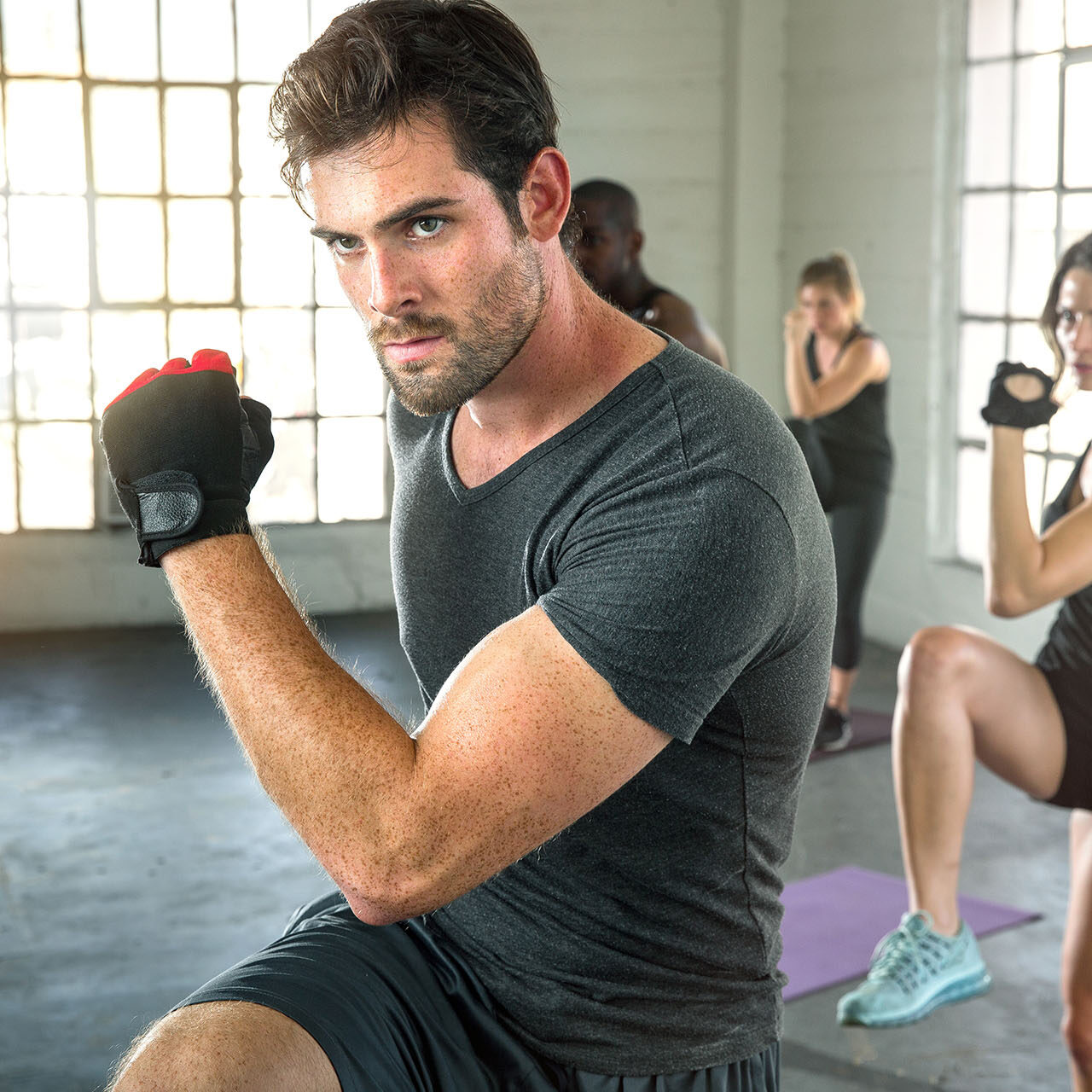 Handsome masculine athlete training exercising with fitness grou